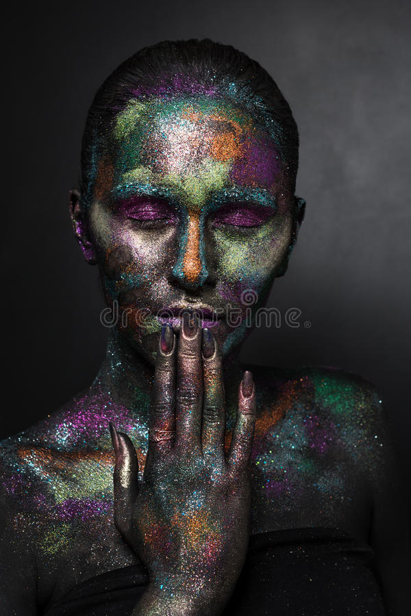 Mujer artística joven en pintura negra y polvo colorido Maquillaje oscuro que brilla intensamente Arte de cuerpo creativo en el t fotografía de archivo
