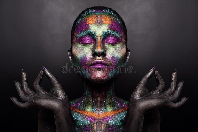 Mujer artística joven en pintura negra y polvo colorido Maquillaje oscuro que brilla intensamente Arte de cuerpo creativo en el t imagen de archivo