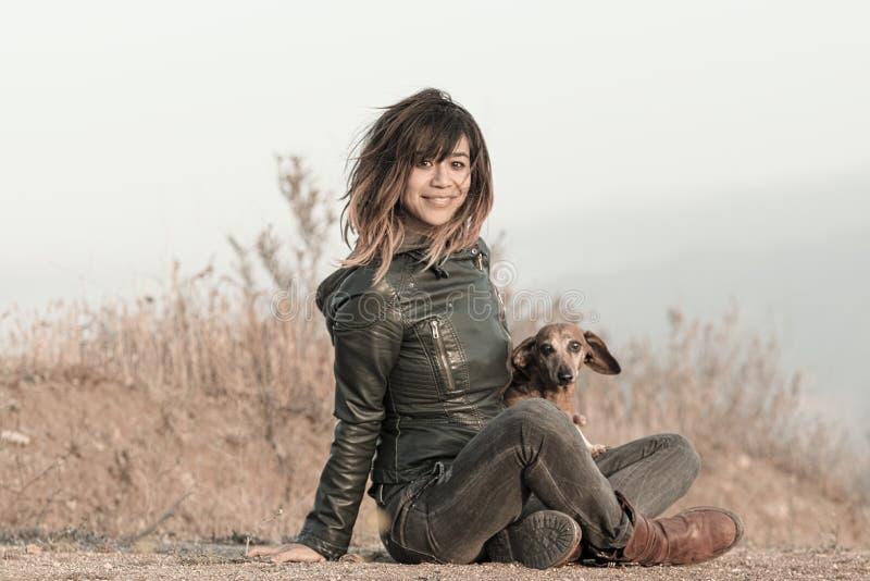 Mujer asentada con la chaqueta de cuero y el perro basset foto de archivo