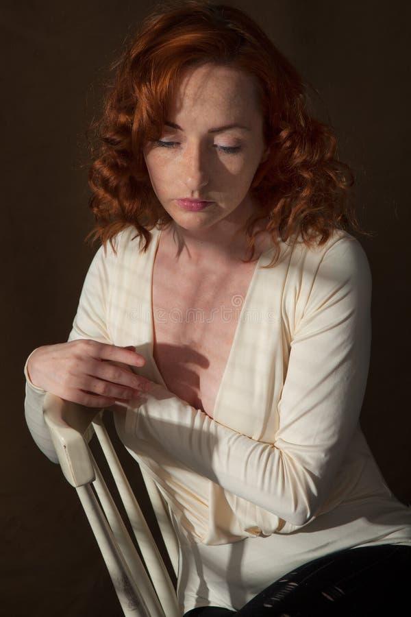 Mujer asentada en de top del blanco fotografía de archivo libre de regalías