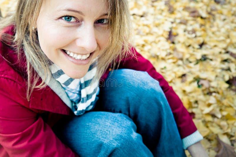 Mujer asentada feliz fotos de archivo libres de regalías