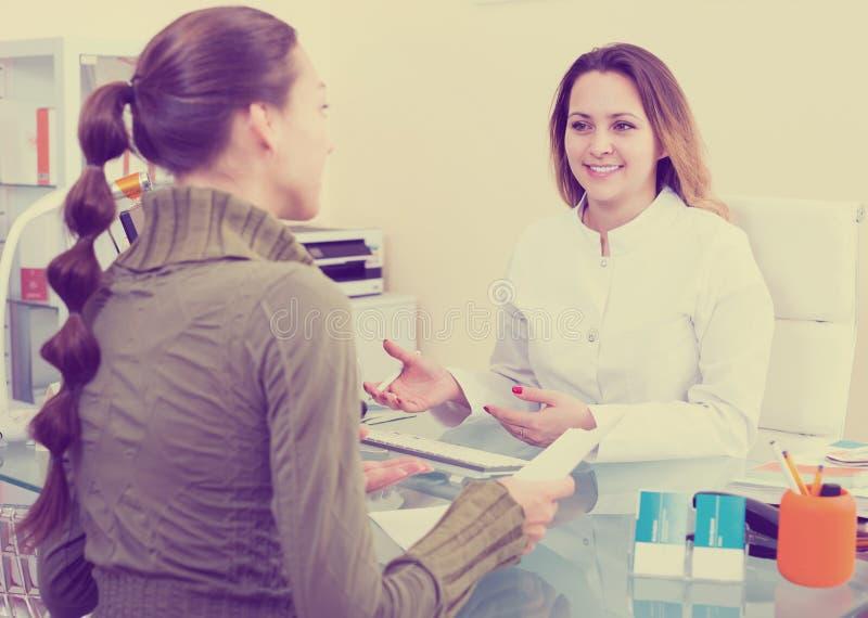 Mujer asesor del visitante del doctor en centro estético fotografía de archivo