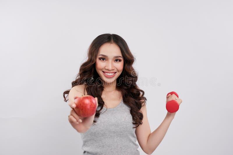 Mujer asiática alegre joven que sostiene pesas de gimnasia y la manzana roja fotos de archivo libres de regalías