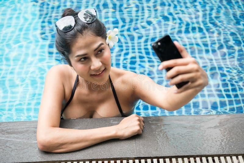 Mujer asiática atractiva con el selfie negro del traje de baño de dos piezas y de las gafas de sol en piscina del th por smartpho fotos de archivo