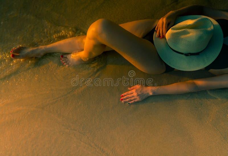 Mujer asiática atractiva con el sombrero que se acuesta en la playa de la arena durante puesta del sol La mujer lleva el traje de fotografía de archivo libre de regalías
