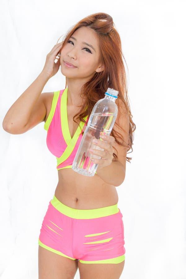 Mujer asiática atractiva con la botella de agua y la toalla después de exercis foto de archivo libre de regalías