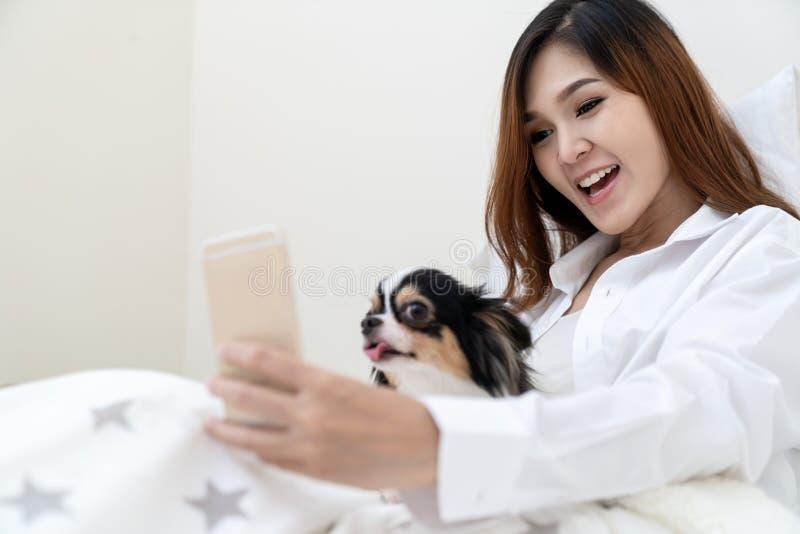 Mujer asiática atractiva feliz joven que juega con el perro de perrito lindo que sonríe en la cámara en smartphone imagen de archivo libre de regalías