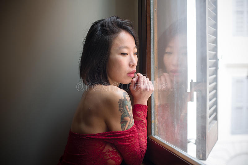 Mujer asiática atractiva hermosa que plantea el bodysuite rojo pensativo fotos de archivo