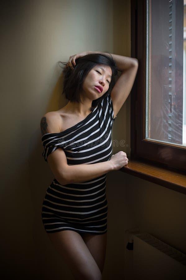 Mujer asiática atractiva hermosa que presenta en la ventana fotos de archivo libres de regalías