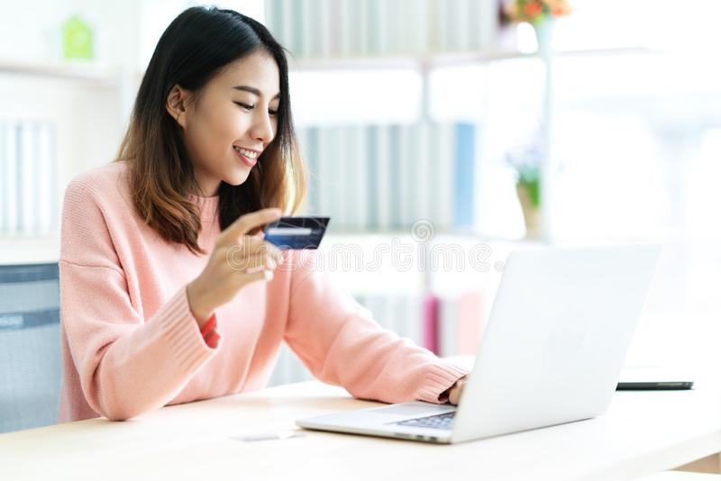 Mujer asiática atractiva joven que sostiene la tarjeta de crédito que se sienta en el teclado que mecanografía de la tabla en el  imágenes de archivo libres de regalías