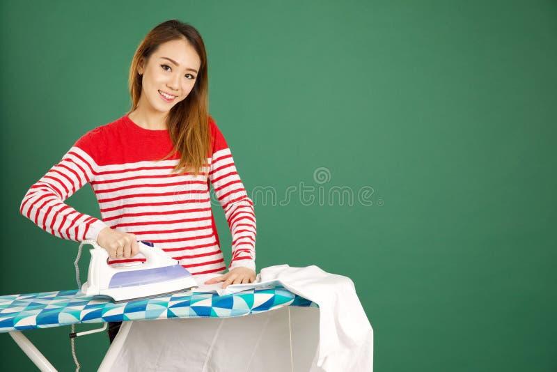 Mujer asiática atractiva que plancha una camisa blanca en un backgrou verde fotos de archivo