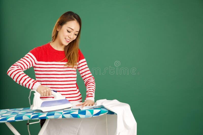 Mujer asiática atractiva que plancha una camisa blanca en un backgrou verde imagen de archivo libre de regalías
