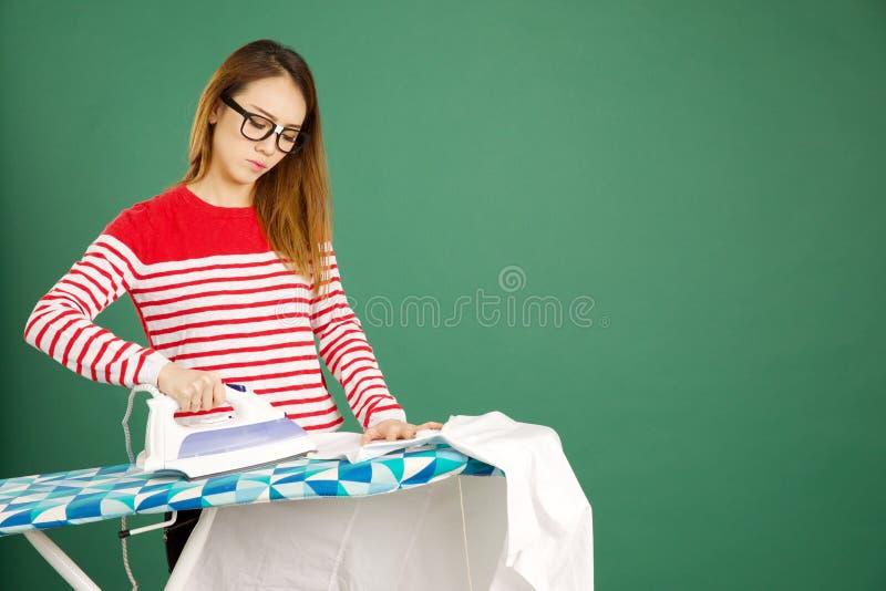 Mujer asiática atractiva que plancha una camisa blanca en un backgrou verde fotografía de archivo