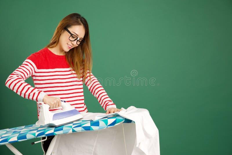 Mujer asiática atractiva que plancha una camisa blanca en un backgrou verde fotografía de archivo libre de regalías