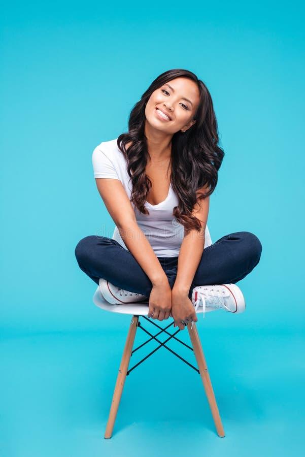 Mujer asiática atractiva sonriente que se sienta en la silla foto de archivo