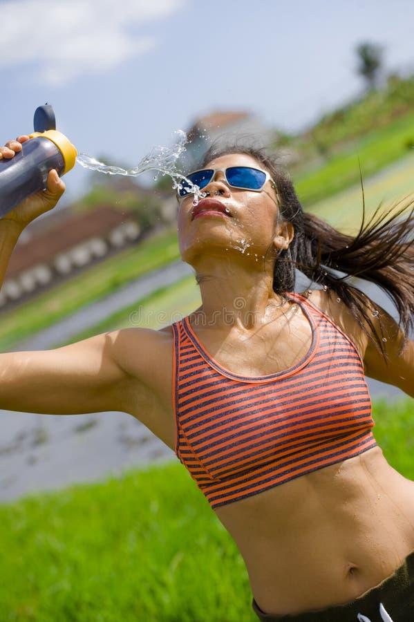 Mujer asiática atractiva y apta del corredor que sostiene el agua potable de la botella isotónica después de entrenar y de funcio imagen de archivo