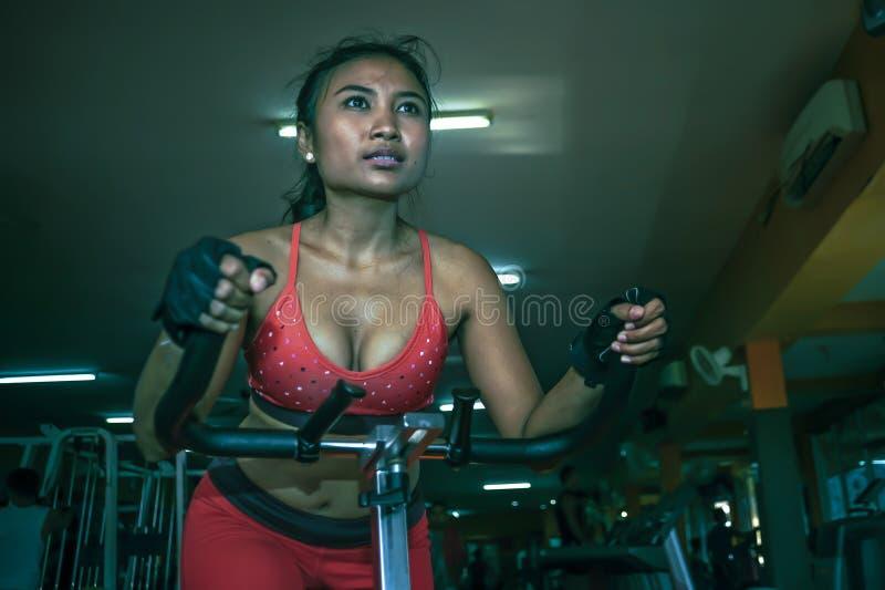 Mujer asiática atractiva y sudorosa joven que entrena difícilmente en el gimnasio usando el engranaje pedaling elíptico de la máq imagen de archivo libre de regalías