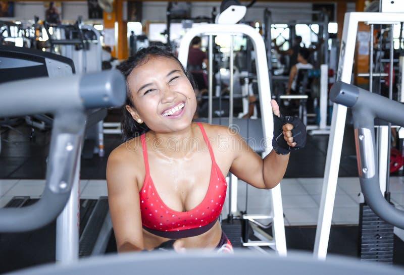 Mujer asiática atractiva y sudorosa que entrena difícilmente en el gimnasio usando el engranaje pedaling elíptico de la máquina e fotos de archivo libres de regalías