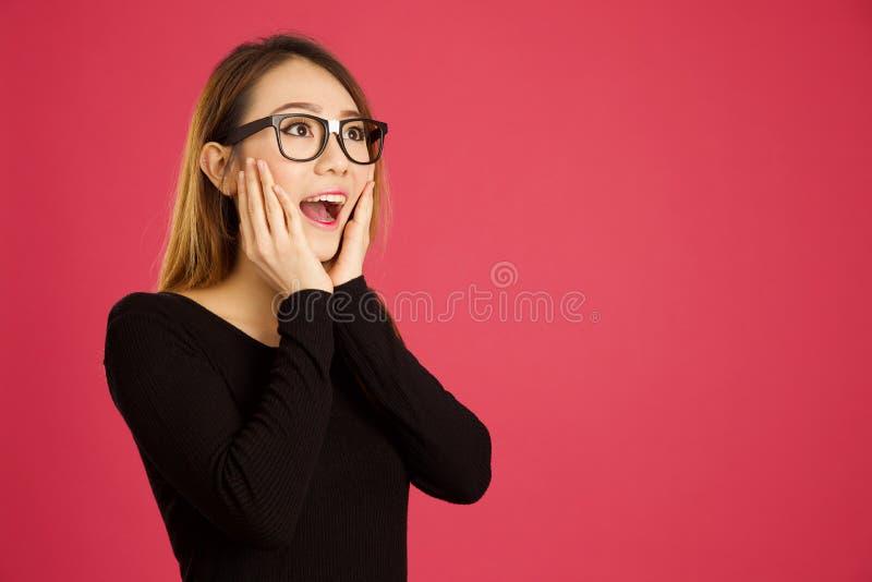 Mujer asiática bastante joven en el estudio que parece chocado imagen de archivo