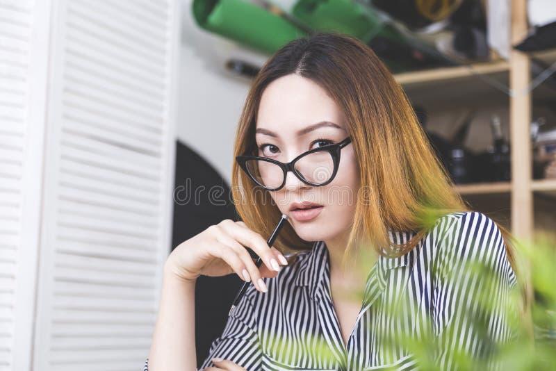 Mujer asiática bochornosa en el lugar de trabajo foto de archivo