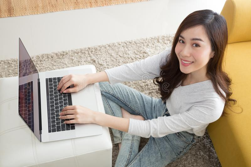 Mujer asiática bonita feliz usando el ordenador portátil que se sienta en piso en sala de estar, hembra independiente usando el c foto de archivo libre de regalías