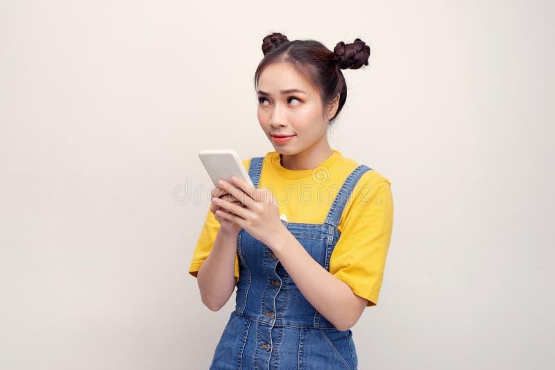 Mujer asiática bonita joven que lleva un overol de los vaqueros y que sostiene smartphone imágenes de archivo libres de regalías