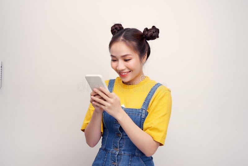 Mujer asiática bonita joven que lleva un overol de los vaqueros y que sostiene smartphone foto de archivo