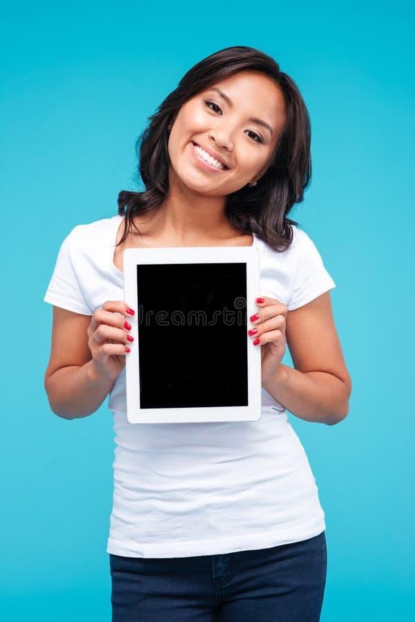 Mujer asiática casual sonriente que muestra la pantalla de tableta en blanco fotografía de archivo libre de regalías