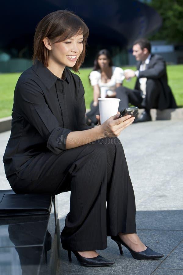 Mujer asiática china Texting y café de consumición fotos de archivo