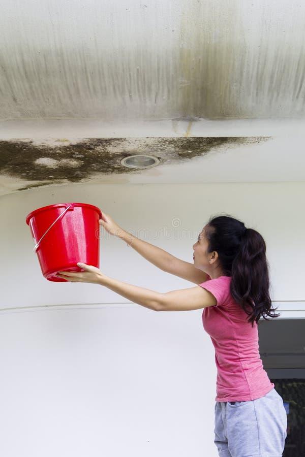 Mujer asiática con el cubo y el techo dañado imagenes de archivo