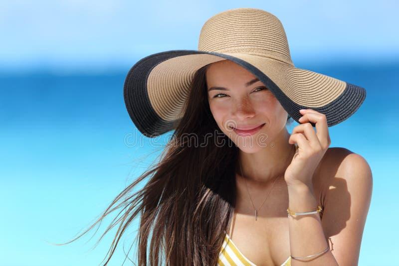 Mujer asiática con el sombrero de la playa para la protección del sol de la cara fotos de archivo