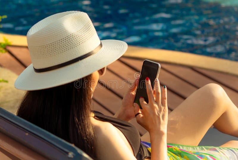 Mujer asiática con el sombrero y el traje de baño que se sientan en silla en el poolside y que usan smartphone el vacaciones de v imagen de archivo libre de regalías