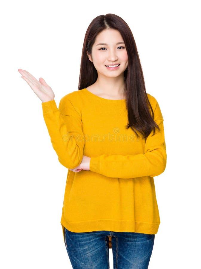 Mujer asiática con la demostración de la mano con la muestra en blanco imagen de archivo
