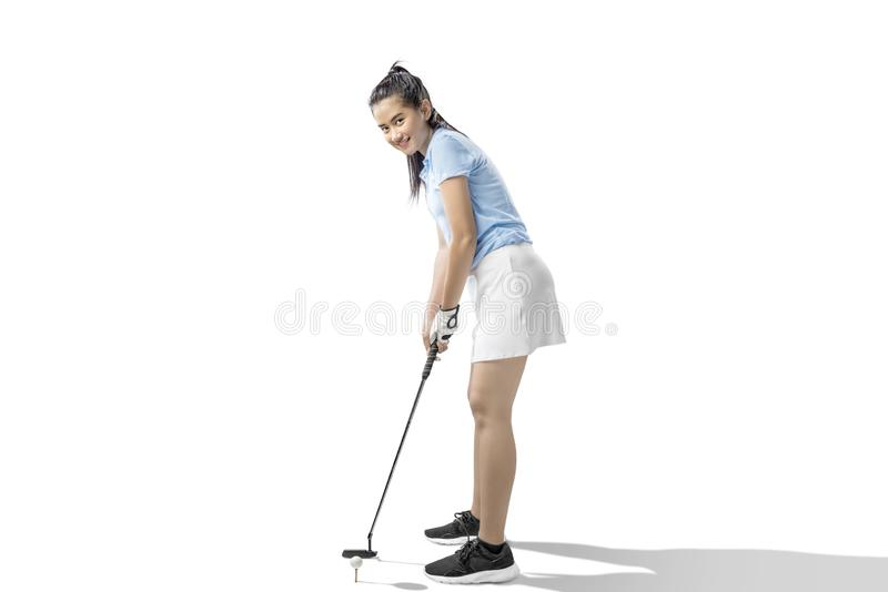 Mujer asiática con un club de golf del putter listo para golpear la bola fotografía de archivo libre de regalías