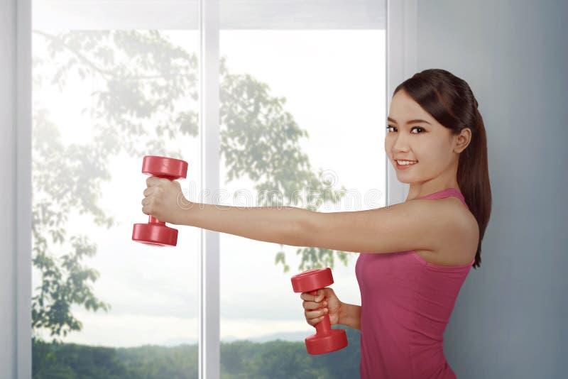 Mujer asiática de la aptitud hermosa que ejercita pesa de gimnasia imagenes de archivo