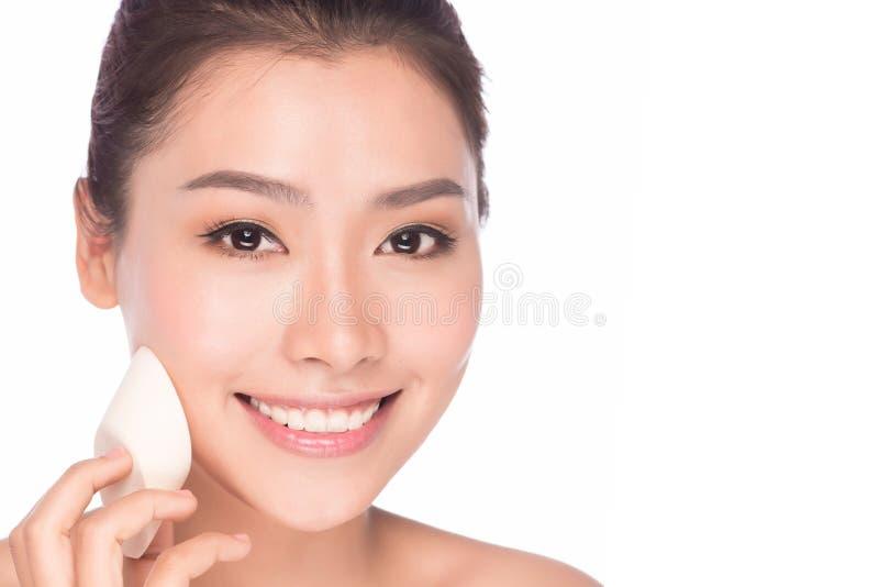 Mujer asiática de la belleza del maquillaje que aplica la cara de la fundación fotografía de archivo libre de regalías