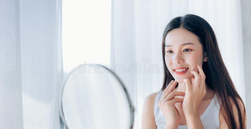 Mujer asiática de la belleza joven que mira la cara clara del control del espejo fotos de archivo