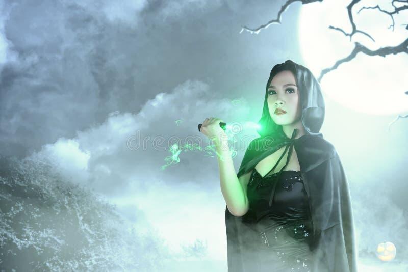 Mujer asiática de la bruja en magia ritual que hace encapuchada negra con un cuchillo fotografía de archivo