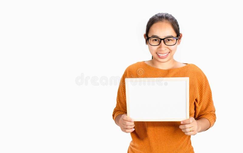 Mujer asiática de la cara feliz que lleva a cabo al tablero blanco en blanco para la copia Placed aislado en un fondo blanco fotografía de archivo