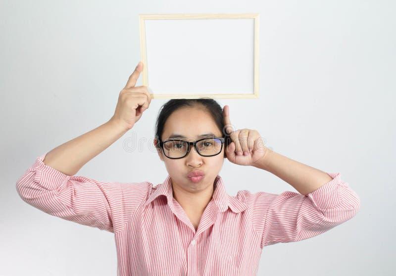 Mujer asiática de la cara feliz que lleva a cabo al tablero blanco en blanco en su cabeza y finger de la demostración que señala  fotos de archivo