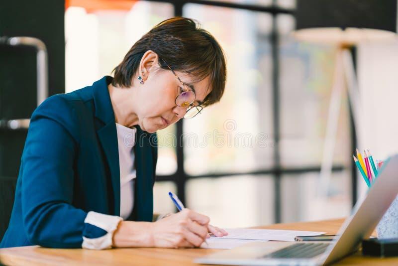 Mujer asiática de la Edad Media que trabaja en papeleo en oficina moderna, con el ordenador portátil Concepto del propietario de  fotos de archivo
