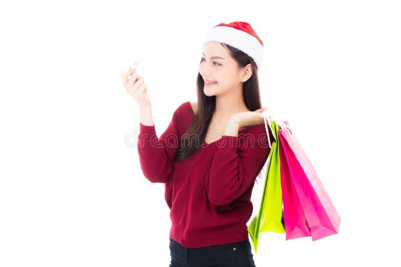 Mujer asiática de la moda feliz con la sonrisa que celebra la bolsa de papel y la tarjeta de crédito que hacen compras imagen de archivo