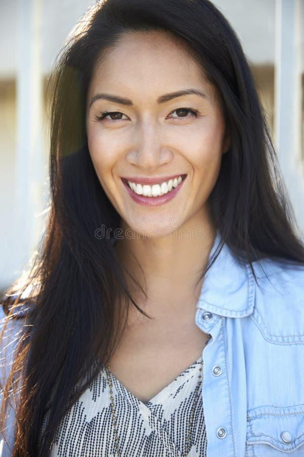 Mujer asiática de la raza mixta joven que sonríe al aire libre, retrato imagenes de archivo