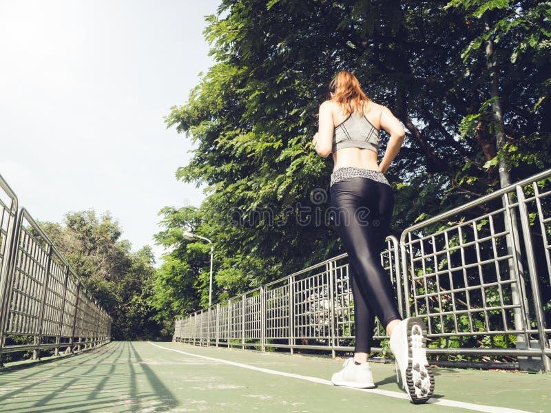 Mujer asiática del deporte joven que corre arriba en las escaleras de la ciudad Gente del deporte de la aptitud y concepto sano d imagen de archivo