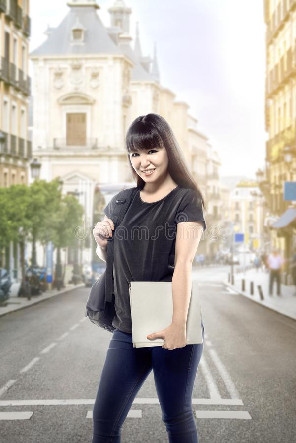 Mujer asiática del estudiante con el libro que lleva de la mochila en la calle de la ciudad que va al campus imagen de archivo