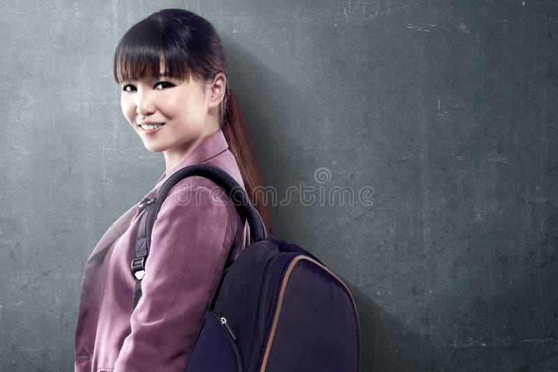 Mujer asi?tica del estudiante con la situaci?n de la mochila y mirar detr?s con el fondo de la pizarra imágenes de archivo libres de regalías
