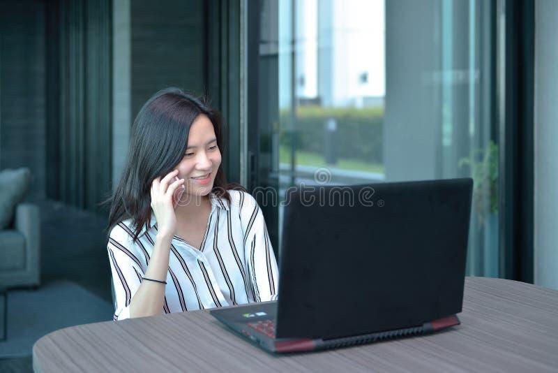 Mujer asiática del negocio casual que llama por teléfono delante de un ordenador portátil en cond foto de archivo