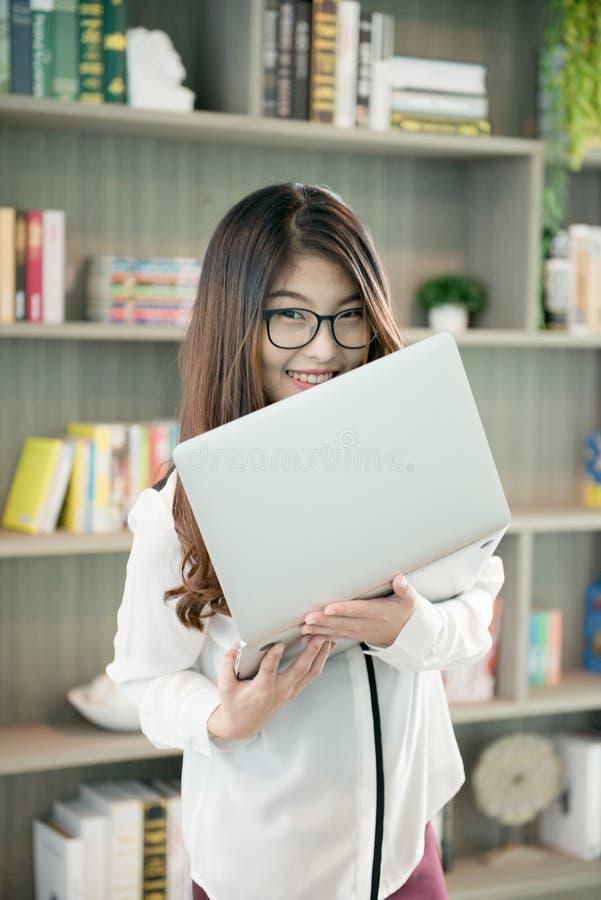 Mujer asiática del negocio que sostiene un ordenador portátil en biblioteca imagenes de archivo