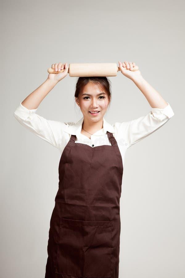 Mujer asiática del panadero en delantal con el rodillo de madera foto de archivo