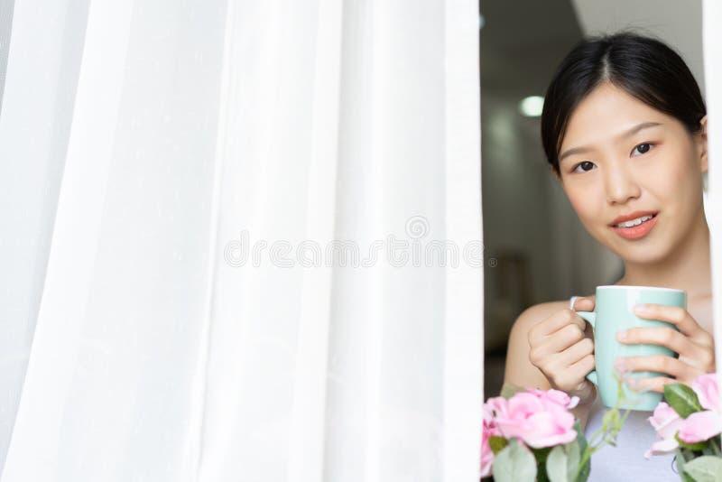 Mujer asiática del retrato que se relaja con café en casa fotografía de archivo libre de regalías